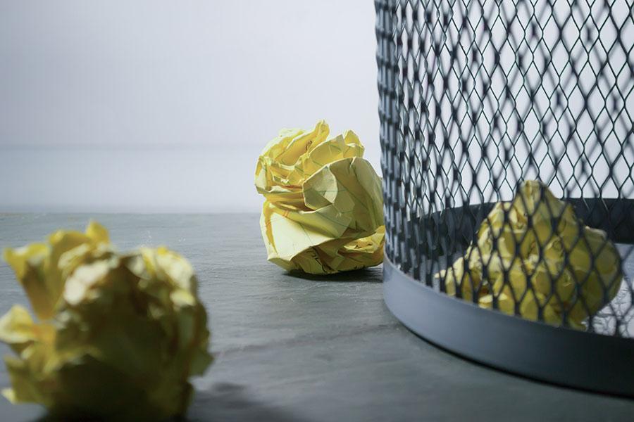 Śmiecenie w biurze - kosz i śmieci na podłodze